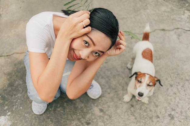 幸せな女は路上で彼女の犬と遊ぶ。