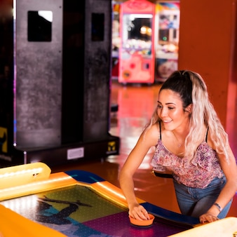 Happy woman playing air hockey
