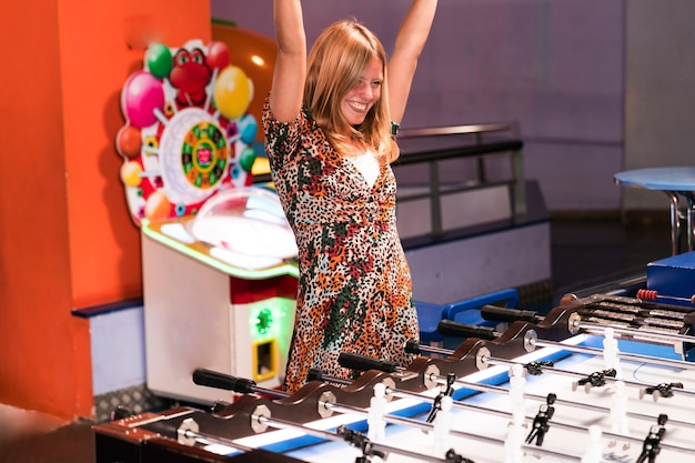 Happy woman playing foosball