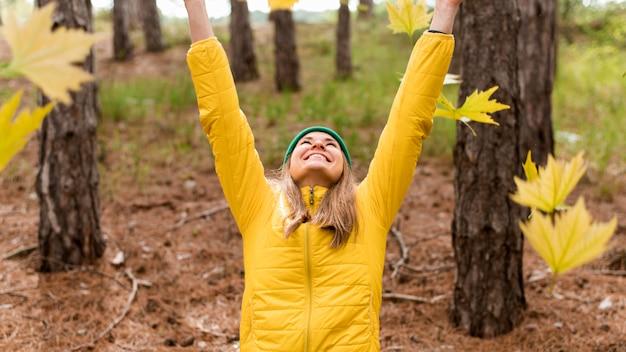 Счастливая женщина играет с осенними листьями