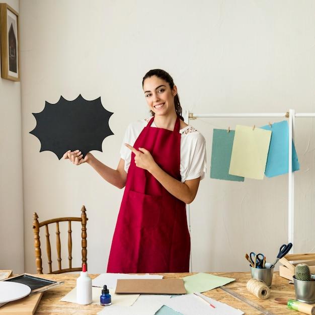紙で作られた言葉の泡を指している幸せな女性