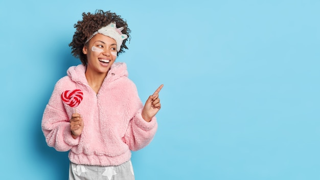 Happy woman points away on copy space feels energized in morning after good sleep indicates aside and advertises product for great nap holds lollipop wears pajama isolated over blue wall
