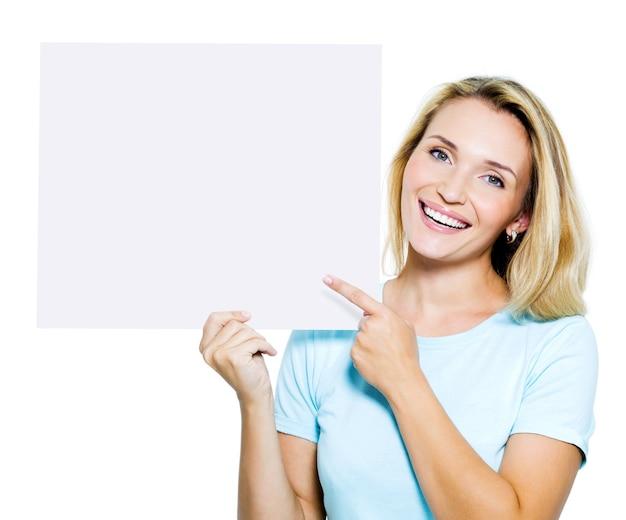 La donna felice indica sulla bandiera in bianco - isolata su bianco