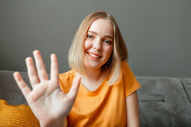 ウェブカメラビューを挨拶する手で幸せな女性の肖像画の波。リビングルームのソファに座ってビデオ通話でこんにちは話をしている若い美女。家族や友人とのリモートコミュニケーション。