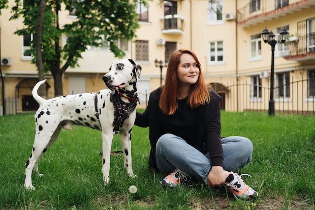 Счастливая женщина позирует и играет со своей далматинской собакой во время прогулки по городу