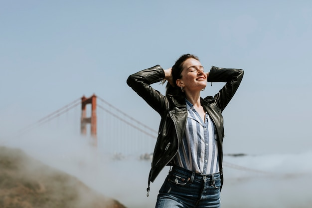 Счастливый женщина позирует для фотографии на мост золотые ворота, сан-франциско