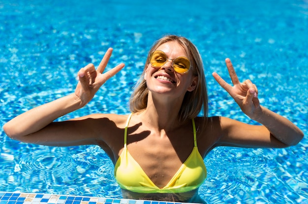 プールでポーズをとって幸せな女