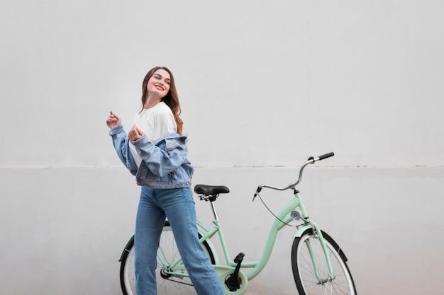 屋外で自転車の横にポーズをとって幸せな女性