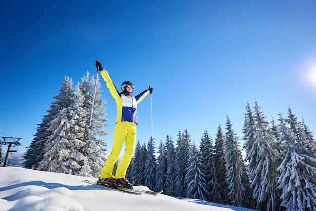 스키를 타기 전에 스키에 포즈를 취하는 행복 한 여자. 스키장에서 화창한 날. 맑고 푸른 하늘, 배경에 눈 덮인 전나무 나무.