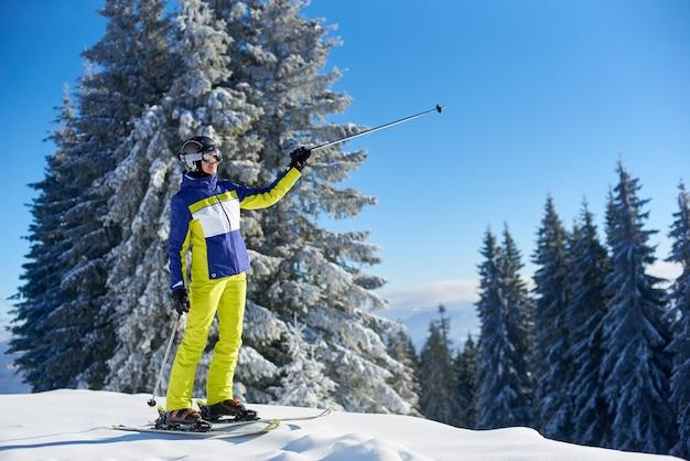 Счастливая женщина позирует на лыжах перед катанием на лыжах. солнечный день на горнолыжном курорте. ясное голубое небо, заснеженные ели на фоне.