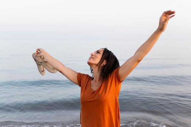Счастливая женщина позирует на пляже
