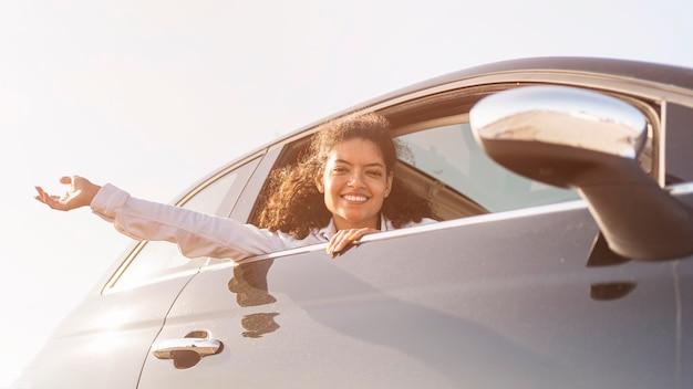 Donna felice che propone fuori dalla finestra