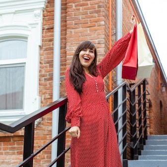 Donna felice che propone all'aperto con un sacco di borse della spesa