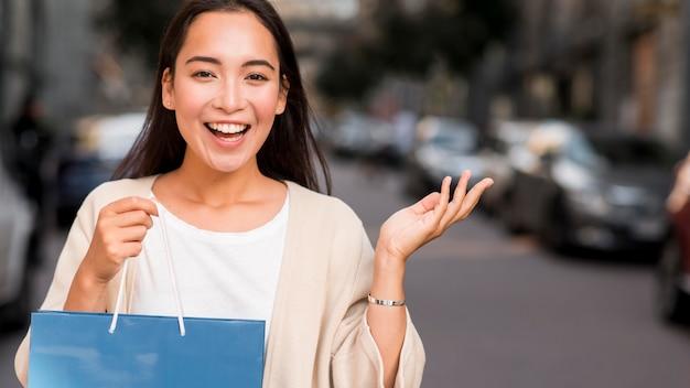Donna felice che propone all'aperto con il sacchetto della spesa e lo spazio della copia