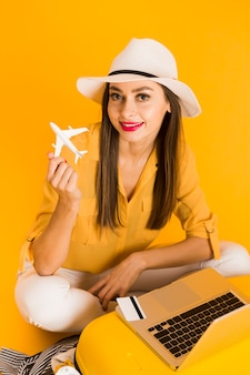 Happy woman posing while holding plane figurine