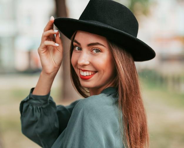 Счастливая женщина позирует в черной шляпе