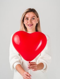 Happy woman posing with balloon for valentines