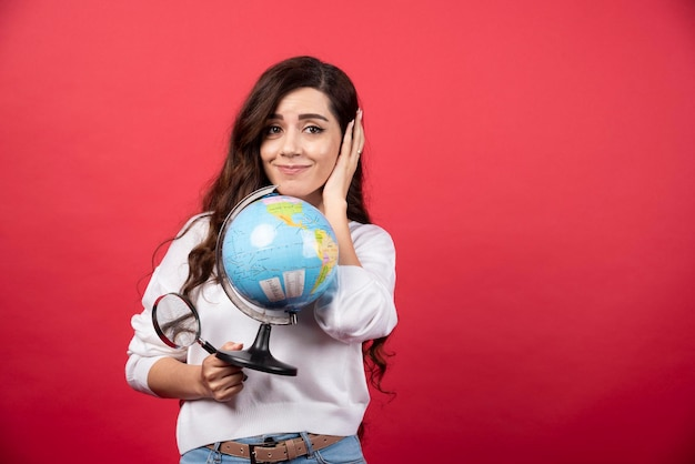 Donna felice che posa con il globo e la lente d'ingrandimento. foto di alta qualità