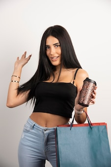 Счастливая женщина позирует с хозяйственными сумками и кофе. фото высокого качества