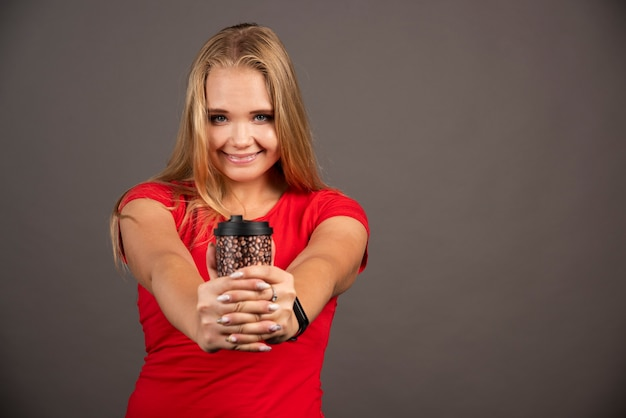 Donna felice in posa con caffè da asporto sulla parete nera.