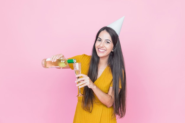 Happy woman pouring drink into glass on pink background
