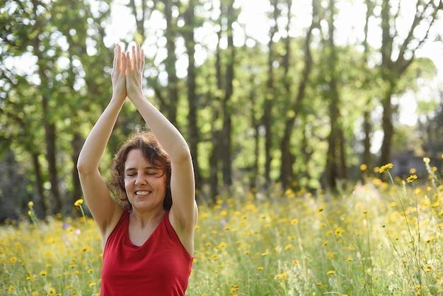 Счастливая женщина упражнениями йоги в лесу