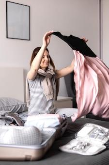 Счастливая женщина кладет одежду и аксессуары в чемодан, собираясь отправиться в отпуск на кровати