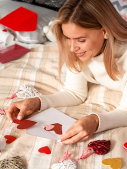 Happy woman putting hearts on envelope