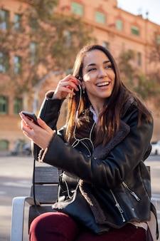 Счастливая женщина надевает наушники своего телефона