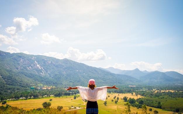 행복 한 여자는 산 위에 그녀의 팔을 제기