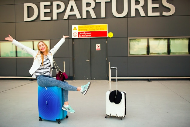 Happy woman raises her hands up sitting on blue suitcase before