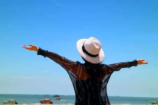 Happy woman raising arms enjoy beautiful sunny day at the sea