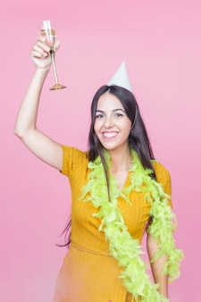 Happy woman raising champagne toast wearing boa and party hat