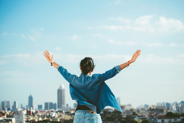 Happy woman raising hands in the city scene background with copy space