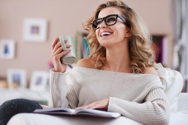 Donna felice che legge una rivista e che beve caffè