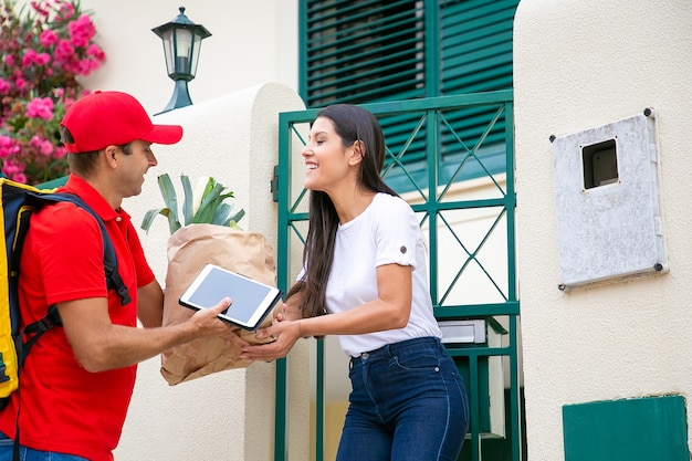 Happy woman receiving food from grocery store, taking package from courier at her gate. shipping or delivery service concept