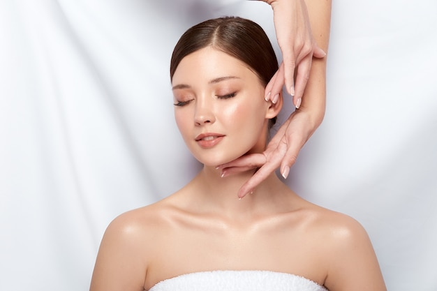 Happy woman receiving massage for her face with eyes closed