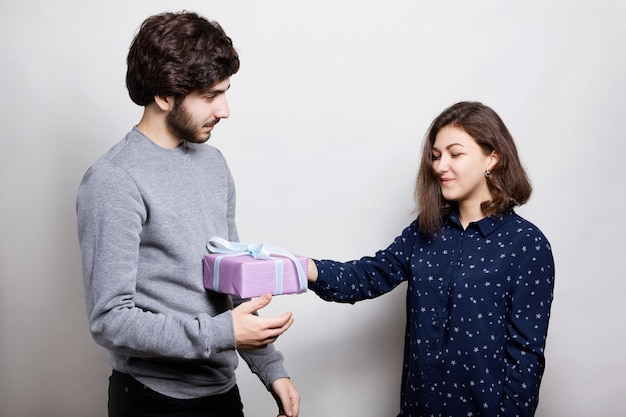 A happy woman receiving a present from her boyfriend. a stylish boy dressed in casual sweater giving her girlfriend a present for bitrhday
