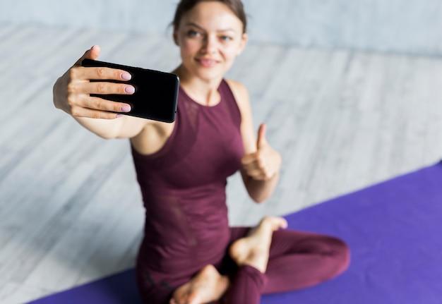 Счастливая женщина записывает ее прогресс тренировки на ее телефоне