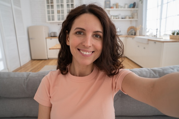 Happy woman recording new content to vlog stretching arm to camera, photographing herself at home.