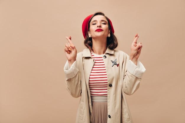 Donna felice in berretto rosso e trincea beige incrocia le dita. bella signora in abito elegante autunno in posa sulla fotocamera su sfondo isolato.