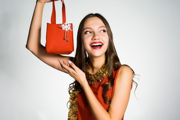 Happy woman in red dress holds in her hand a small handbag