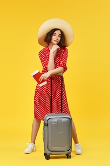 Happy woman in red dress with gray suitcase and and passport going traveling on yellow background.