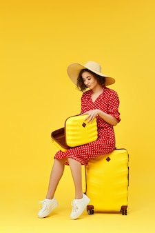 Happy woman in red dress with open suitcase going traveling on yellow background.