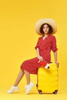 Happy woman in red dress with passport sitting on a suitcase on yellow background.