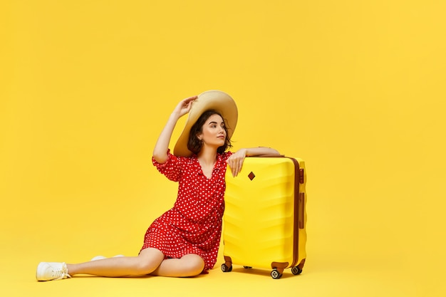 Happy woman in red dress with suitcase going traveling on yellow background. concept of travel. copy space