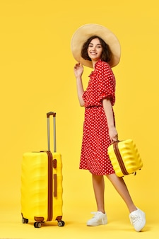 Happy woman in red dress with suitcase going traveling on yellow background. concept of travel.