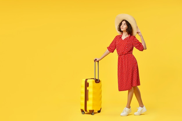 Happy woman in red dress with suitcase going traveling on yellow background. copy space