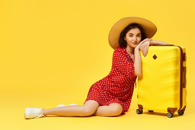Happy woman in red dress with suitcase going traveling on yellow background.