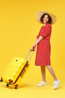 Happy woman in red dress with walking with suitcase going traveling on yellow background.
